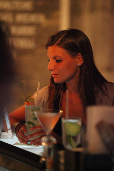 A lady stands at the Justincase bar with a cocktail in her hand