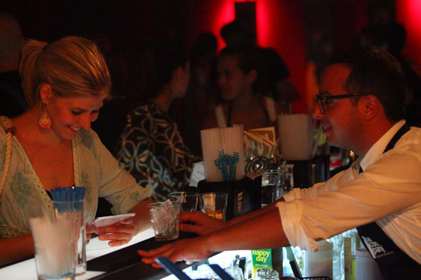 A lady chooses a cocktail from the menu while the barman suggests a drink