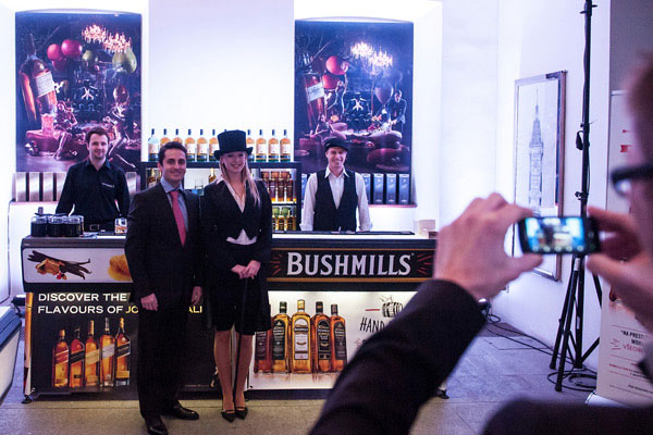 A couple poses for a photo in front of a Bushmills bar